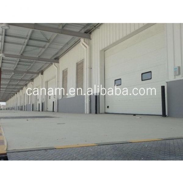 Sectional industrial lifting door with door and wicket #1 image